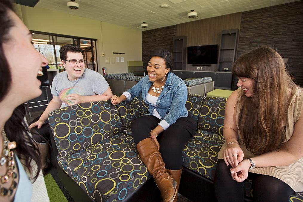 Four Keuka College students sit and laugh in their residence hall lounge.