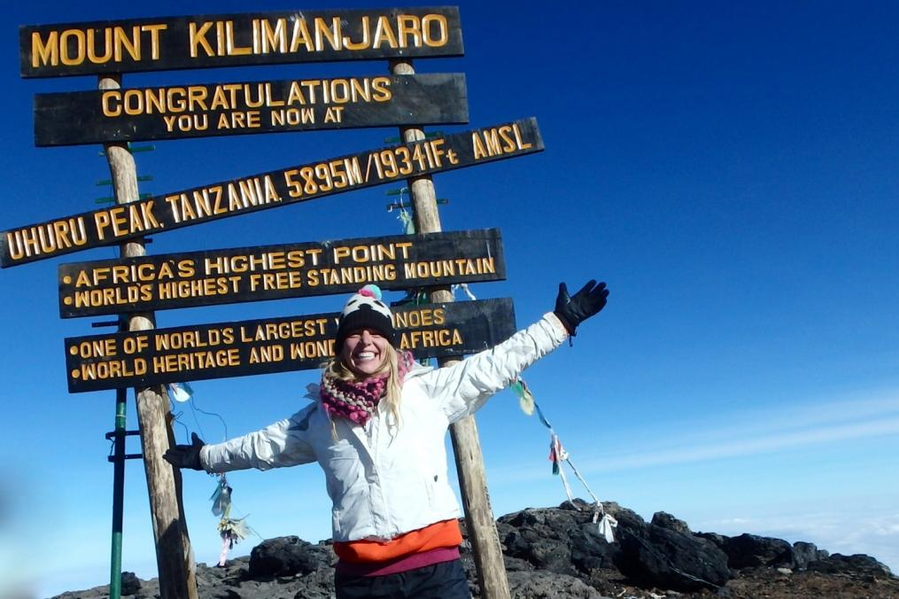 Student stands at the top of Mount Kilimanjaro, the highest point in Africa.