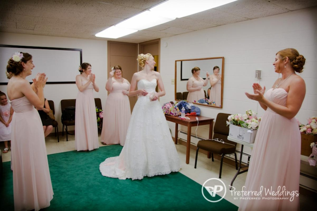 Bridesmaids standing around a bride in her dress before a ceremony