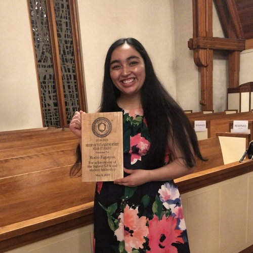 Rocio Figueroa posing with an award in the Chapel